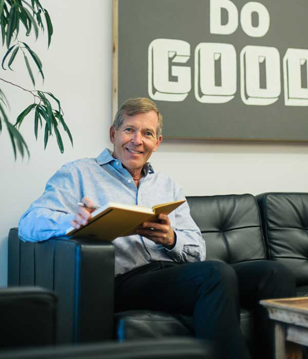 Chris Cipoletti sitting on black couch at the office entrance and reviewing meeting notes